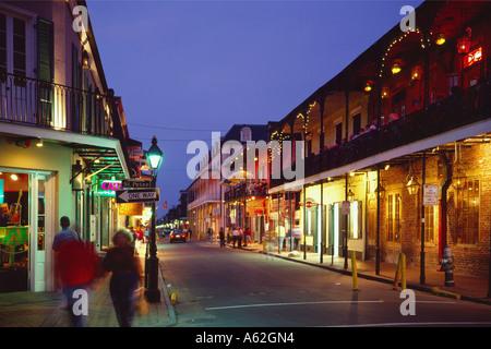 Group of people walking along illuminated street, Bourbon Street, New Orleans, Louisiana, USA - Stock Photo