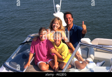 Portrait of happy family on motor boat having fun and relaxing outdoors together - Stock Photo