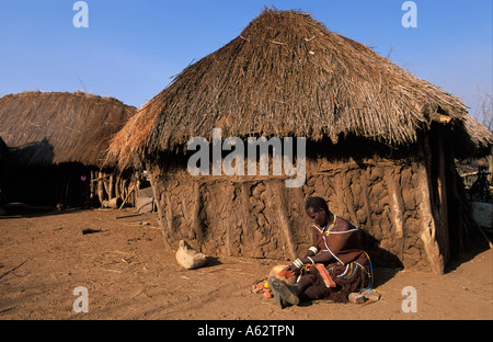 Barabaig women making a leather dress in front of her mud and thatch homestead Hanang area Tanzania - Stock Photo