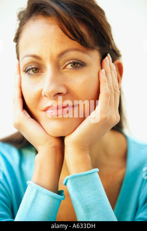 Portrait of a mid adult woman with her head in her hands - Stock Photo