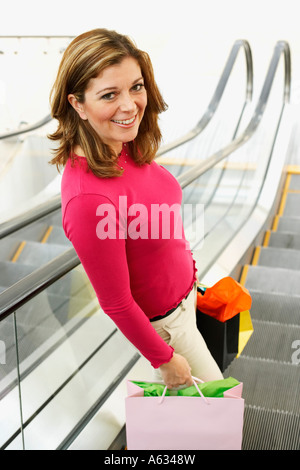 Portrait of a mature woman holding shopping bags on an escalator - Stock Photo