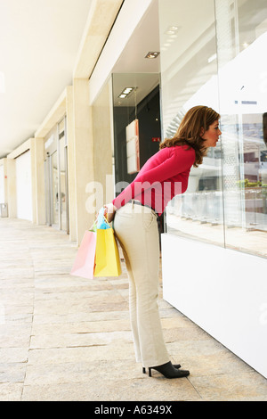 Side profile of a mature woman looking at the window display of a store - Stock Photo