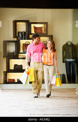 Mid adult man and a mature woman carrying shopping bags - Stock Photo