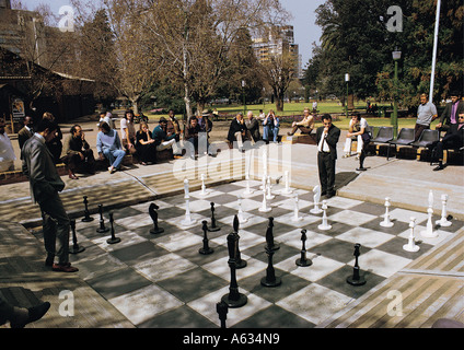 Playing chess on giant chess set in Joubert Park in Johannesburg South Africa Mixed race people look on - Stock Photo