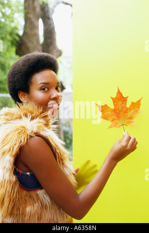 Portrait of a young woman holding a maple leaf and smiling - Stock Photo