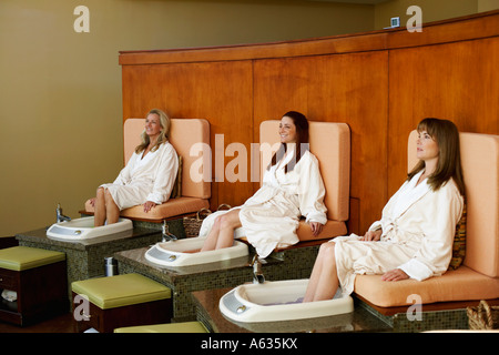 Three mature women getting pedicure in a beauty parlor - Stock Photo
