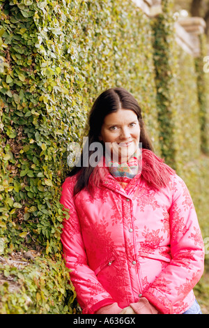 Portrait of a young woman leaning against an ivy covered wall and smirking - Stock Photo