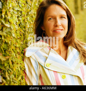Portrait of a young woman leaning against an ivy covered wall - Stock Photo
