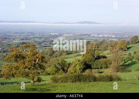 Autumn mist in the Severn Vale viewed from the Cotswold scarp at Edge, Gloucestershire - Stock Photo