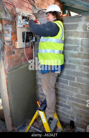 AN ELECTRICIAN REMOVES OLD ELECTRICITY FUSE BOXES AND INSTALLS A MEMERA CONSUMER UNIT UK - Stock Photo