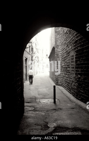 European street through archway with a man walking in the distance Barcelona Spain - Stock Photo