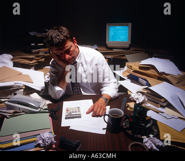 STRESSED SMALL BUSINESS MAN WITH COMPUTER SEATED AT DESK SURROUNDED BY PILES OF PAPERWORK STRUGGLING TO SURVIVE - Stock Photo