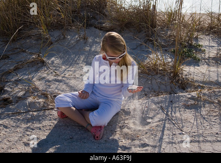 Child letting sand run through her fingers - Stock Photo