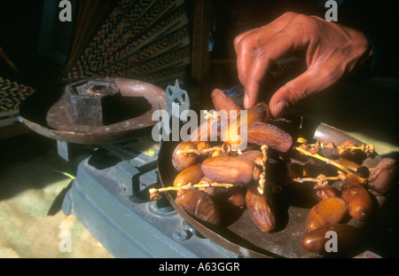 Close up of a shopkeeper's hands weighing dates on an old pair of scales in Tozeur, Tunisia - Stock Photo