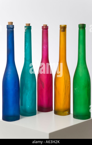Still life with five slender hand made bottles with corks in blue turquoise red yellow and green on a plinth in - Stock Photo
