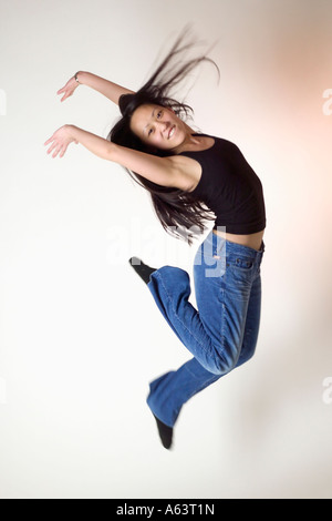 Asian woman leaping for joy - Stock Photo
