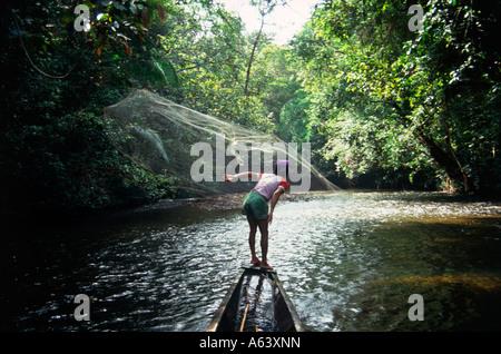 infant boy fishing with net in jungle lagoon near city of kuching island of borneo state of sarawak malaysia - Stock Photo