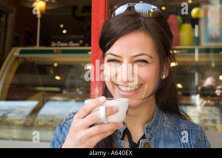 Beautiful young Turkish woman drinking cup of cappuccino coffee at a cafe, London England UK