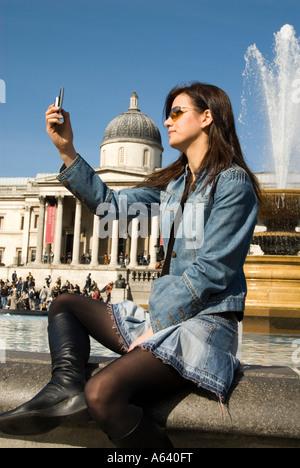 Beautiful young woman tourist taking photos with mobile phone camera at Trafalgar Square London England UK - Stock Photo