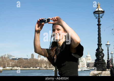 Beautiful young woman tourist taking photos London England UK - Stock Photo