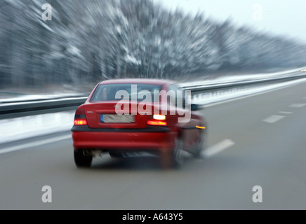 Car drives very fast on a wet german Autobahn in winter - Stock Photo