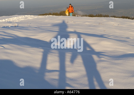 Man and child casting shaddows on the snow Woman with child ascending to Mount Zwiesel view to the Lengries valley - Stock Photo
