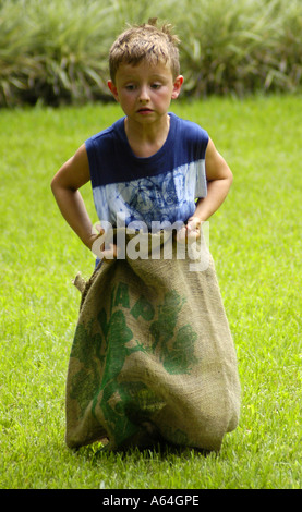 Boy determined look sack race - Stock Photo