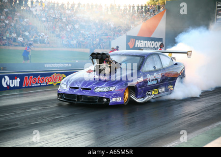 Australian Holden Monaro 'Top Doorslammer' drag car performing burnout prior to racing on the [quarter mile] - Stock Photo