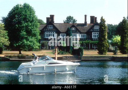A motor cruiser passes a large house on the River Thames at Remenham in Berkshire England UK - Stock Photo