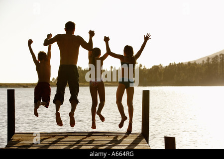 Rear view of father and children jumping off a pier holding hands - Stock Photo