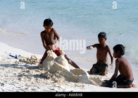 Local boys building a castle in the white beach sands of Boracay, Philippine Islands - Stock Photo