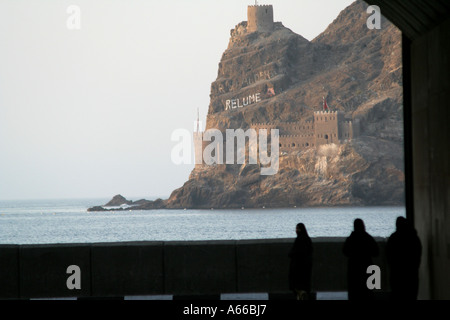 View through a tunnel of Omani women and a cliffside watchtower, Muscat, Oman - Stock Photo