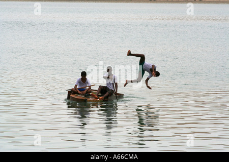 Boy dives off of a makeshift boat, Sur, Oman - Stock Photo