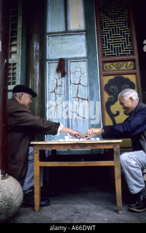 Two elderly men playing game of draughts in front of a temple entrance in the Xiu Shan park. Tonghai, Yunnan province, - Stock Photo