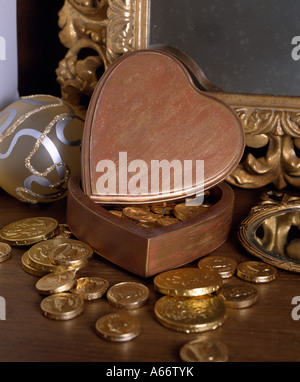 Foil-covered chocolate coins and heart-shaped wooden box in front of gilt mirror frame - Stock Photo