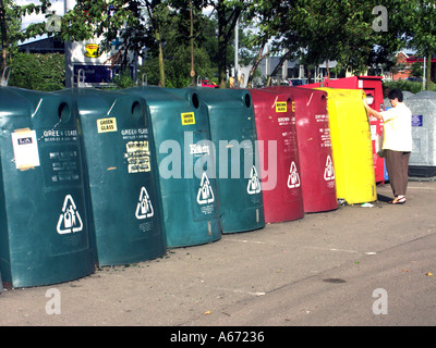 Model released housewife placing items in recycle bins in UK supermarket car park recycling centre - Stock Photo