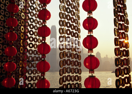 A curtain of Chinese New Year decorations frame a view of Victoria Harbour from Tsim Sha Tsui in Hong Kong - Stock Photo