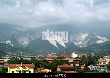 Residential areas below a summer view of white quarry workings in Apuan Alps producing famous Carrara marble for - Stock Photo