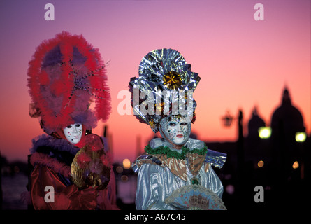 Two masks at sunset Carnival in Venice Italy - Stock Photo