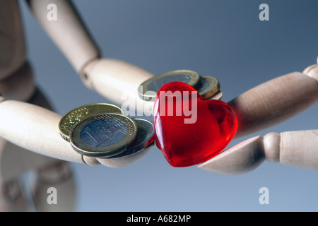 Two wooden figures giving each other a red heart and a Euro coin - Stock Photo