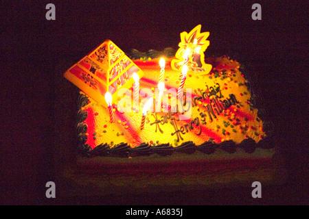 Burning candles on a Yami Yugi Yu-Gi-Oh theme birthday cake for Henry and William.  Burnsville Minnesota USA - Stock Photo