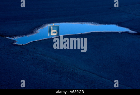 Image of blue parking lot traffic sign reflecting from a small pool of water on tarmac - Stock Photo