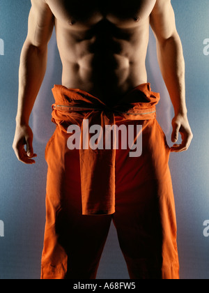 Close up of a bare chested muscular man wearing orange martial arts suit - Stock Photo