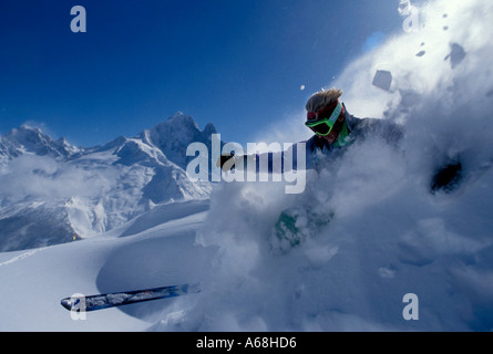 Man skiing a speed with clouds of snow around him - Stock Photo