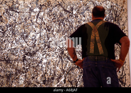 man with matching braces standing in front of Jackson Pollock painting at the recently re-opened Museum of modern - Stock Photo