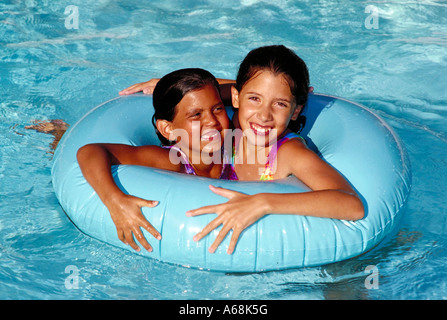 Girls playing with a float tube in a swimming pool - Stock Photo