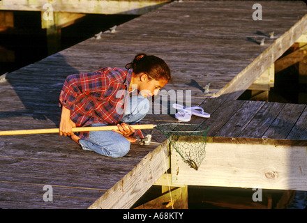 Young girl crabbing from the dock - Stock Photo