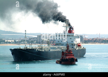 Ship discharging black smoke with tug arriving at Port of Palma Mallorca - Stock Photo