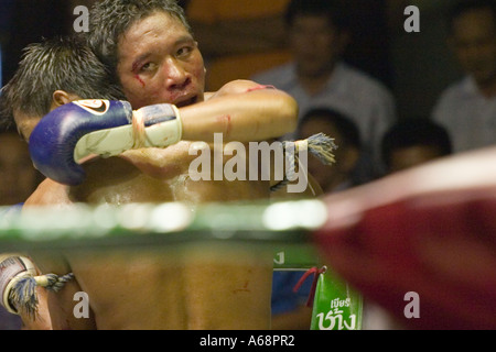 Fighters grappling during the last round of a Muay Thai fight (Rajadamnern stadium, Bangkok, Thailand). - Stock Photo