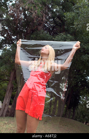 Pretty blond female model holding plastic sheet over face showing she is cut off from the real world - Stock Photo
